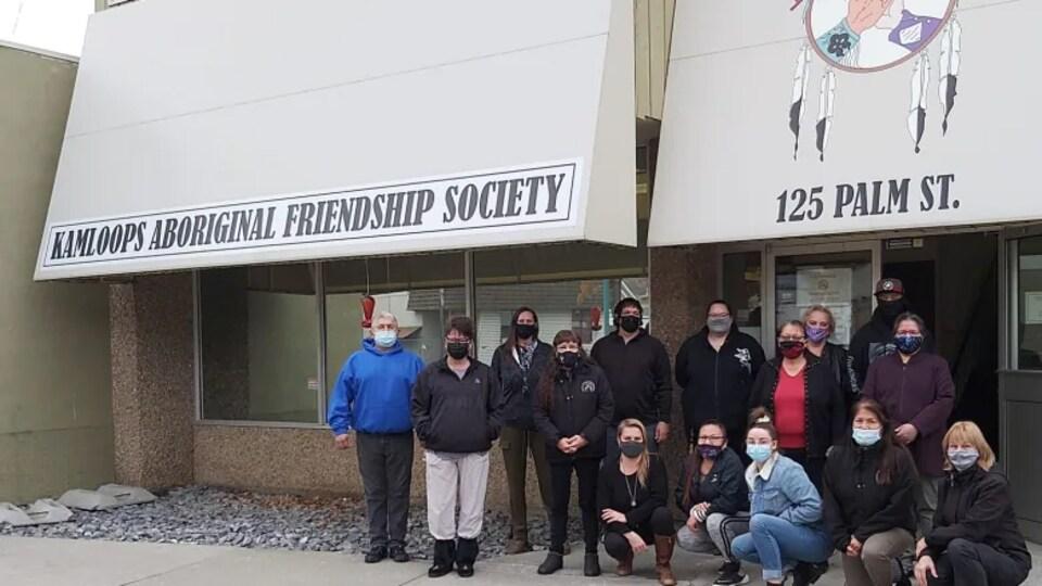 Un groupe de personnes devant le bâtiment de la société.