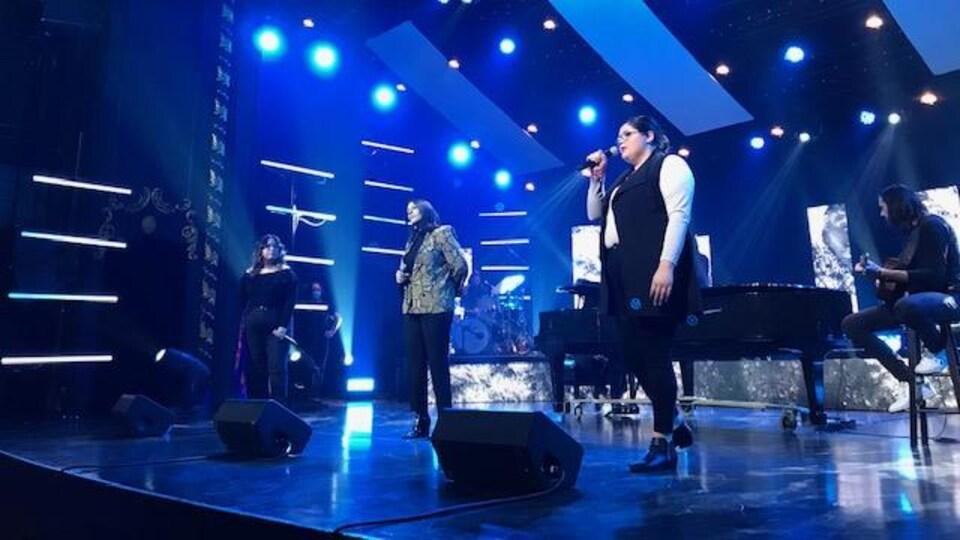 Trois chanteuses sur une scène.