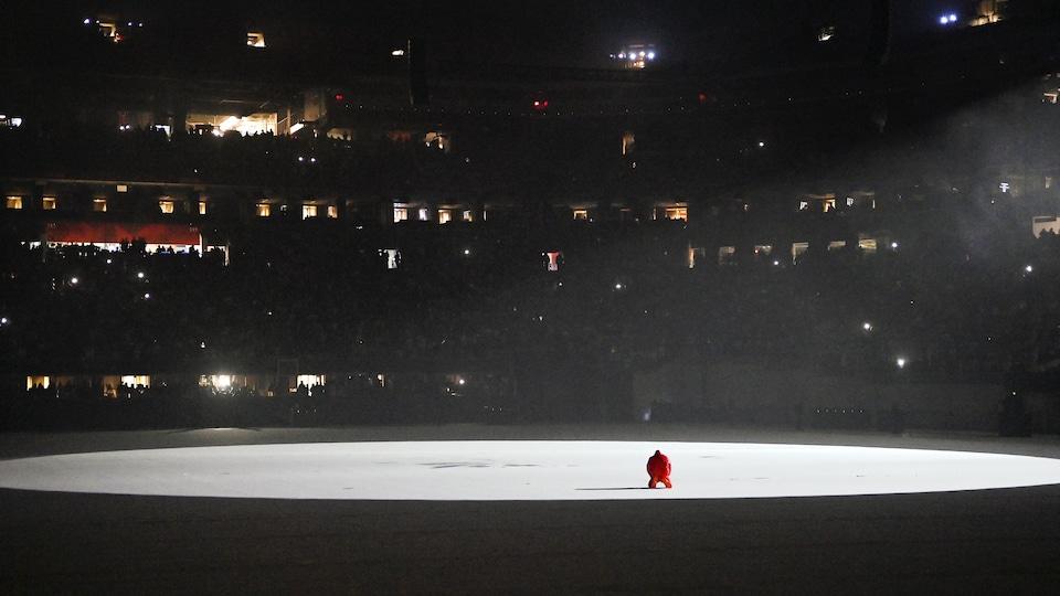 Un homme habillé en rouge est agenouillé au centre d'une énorme scène blanche, devant des milliers de spectateurs.