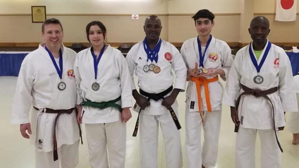 Cinq karatékas sont pris en photo côte à côte, des médailles autour du cou.