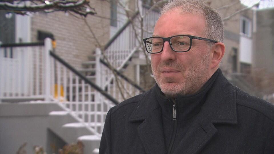 Un homme devant un immeuble à logements à Montréal.