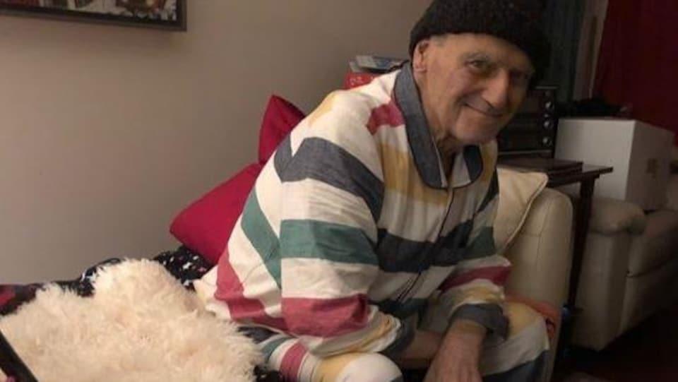 Karel Pekarek est en pyjama, assis sur son lit.