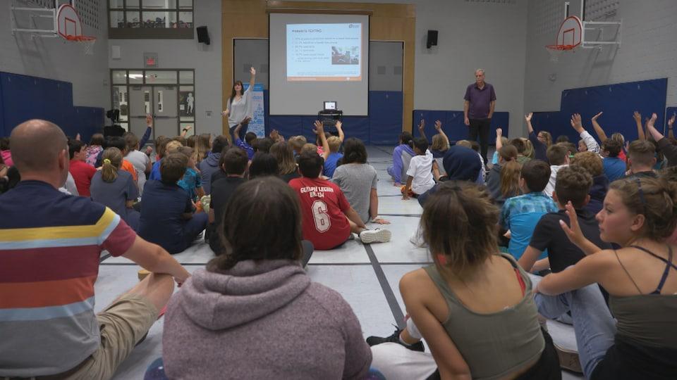 Des élèves assis dans un gymnase lors d'une présentation.