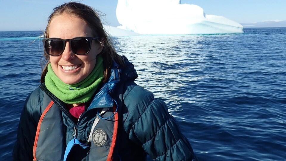 Une femme pose devant un iceberg, au Nunavut.