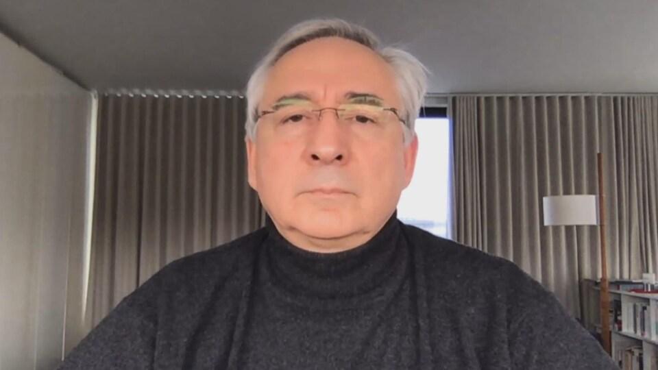 Un homme qui porte un col roulé est assis devant une caméra.