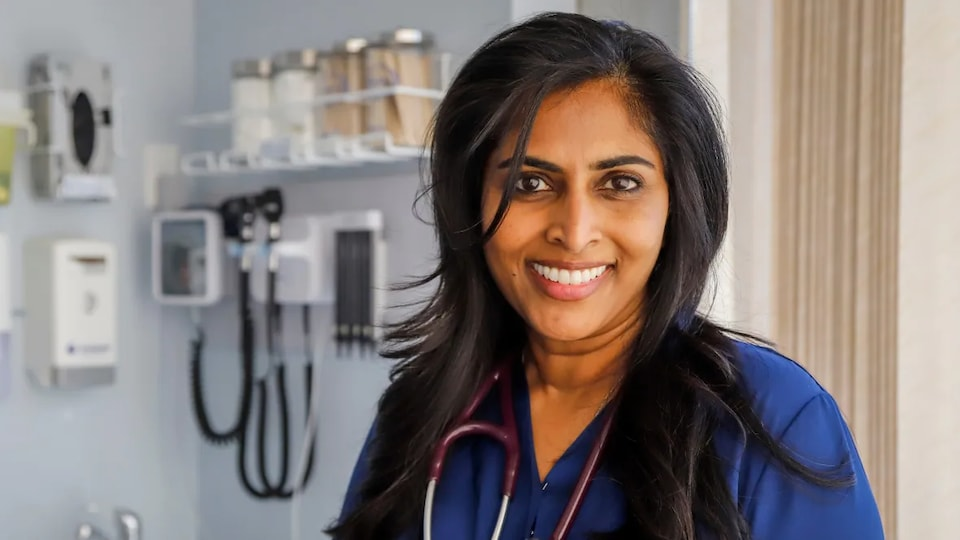 Karina Pillay stéthoscope au cou pose dans une salle médicale.