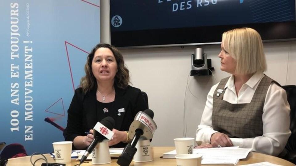 Deux femmes devant des micros en conférence de presse.