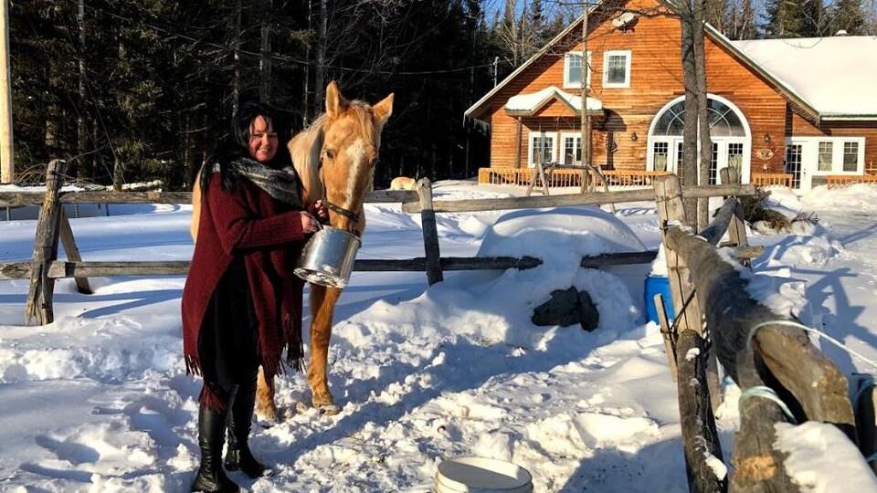 Karine Veilleux nourrit son cheval.