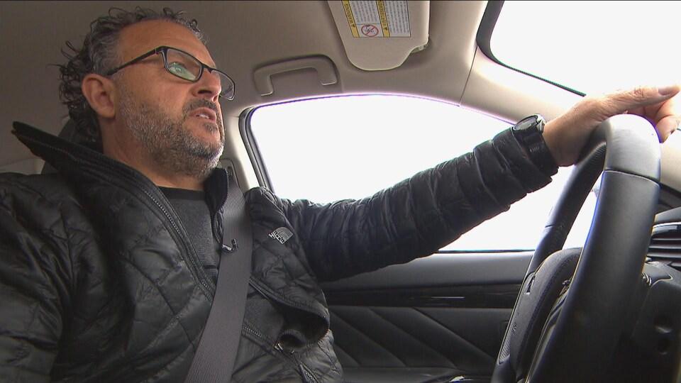 Homme conduisant une voiture sur la route.