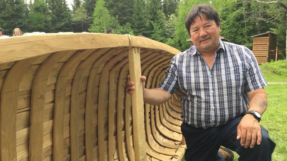 Un homme d'origine autochtone pose avec un canot fait à la main, souriant.