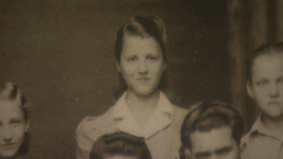 Une adolescente au milieu d'un groupe de jeunes sourit, sur une photo d'époque.