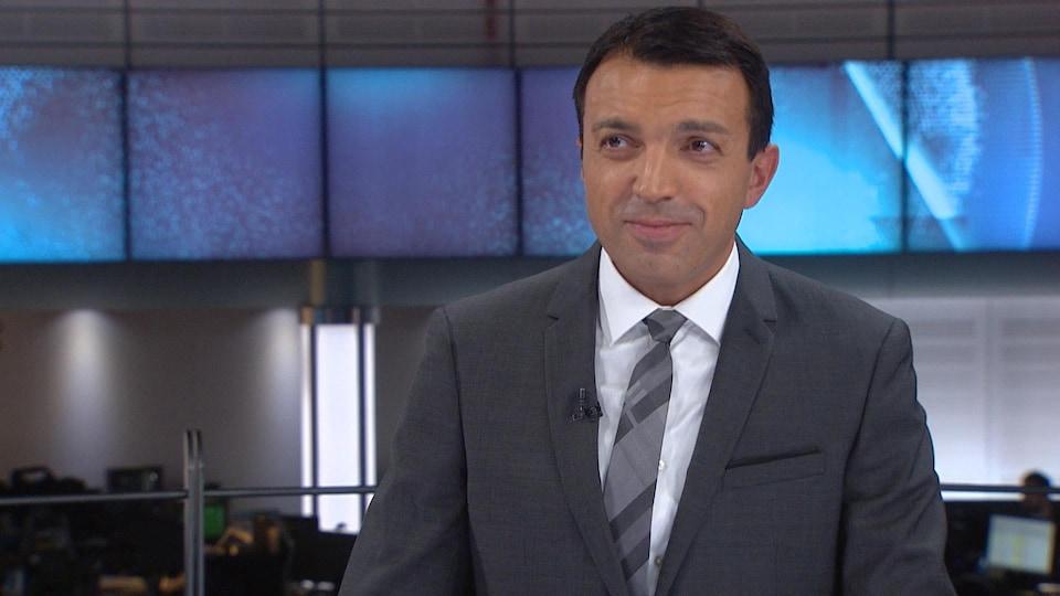 Un homme basané aux cheveux courts qui porte un veston, une blouse et une cravate regarde vers sa droite en souriant un peu.