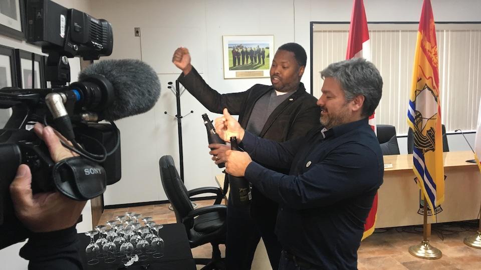 Le conseiller Kassim Doumbia et le directeur des loisirs, Jules DeSylva, ouvrent des bouteilles de vin mousseux