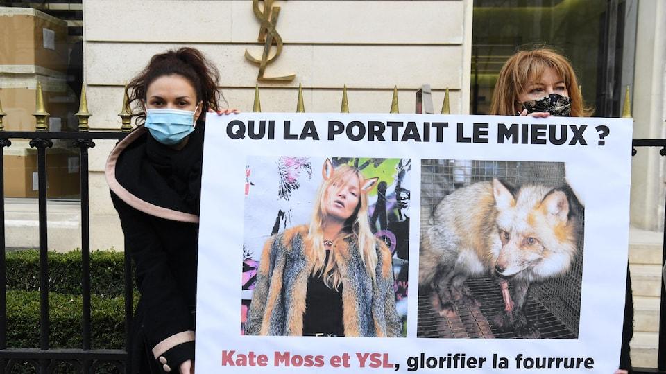 Deux militants de Peta tiennent une affiche montrant un renard et Kate Moss portant un manteau de fourrure.