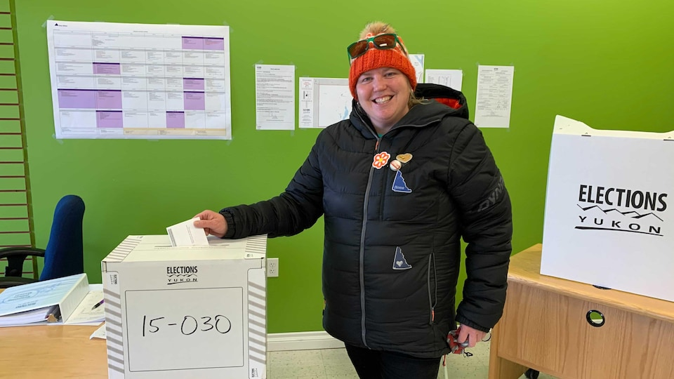 Une femme portant une tuque orange pose en tenant un bulletin de vote à la main.