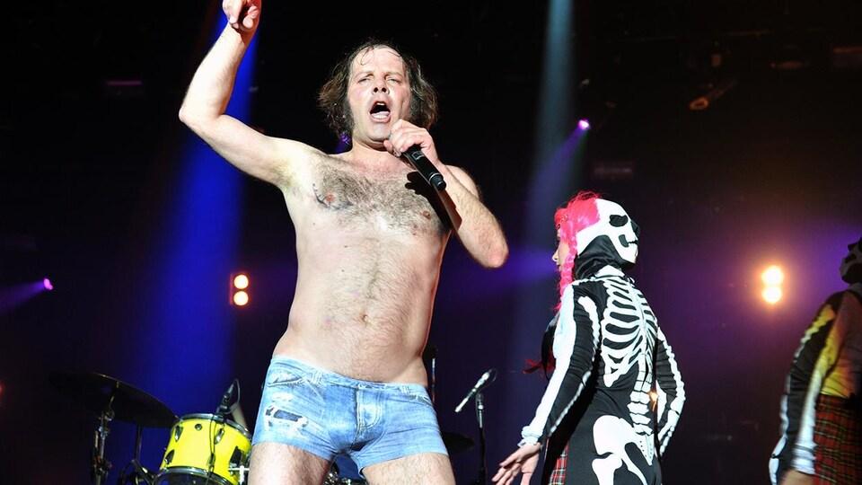 Philippe Katerine chante sur scène, torse nu et en short.