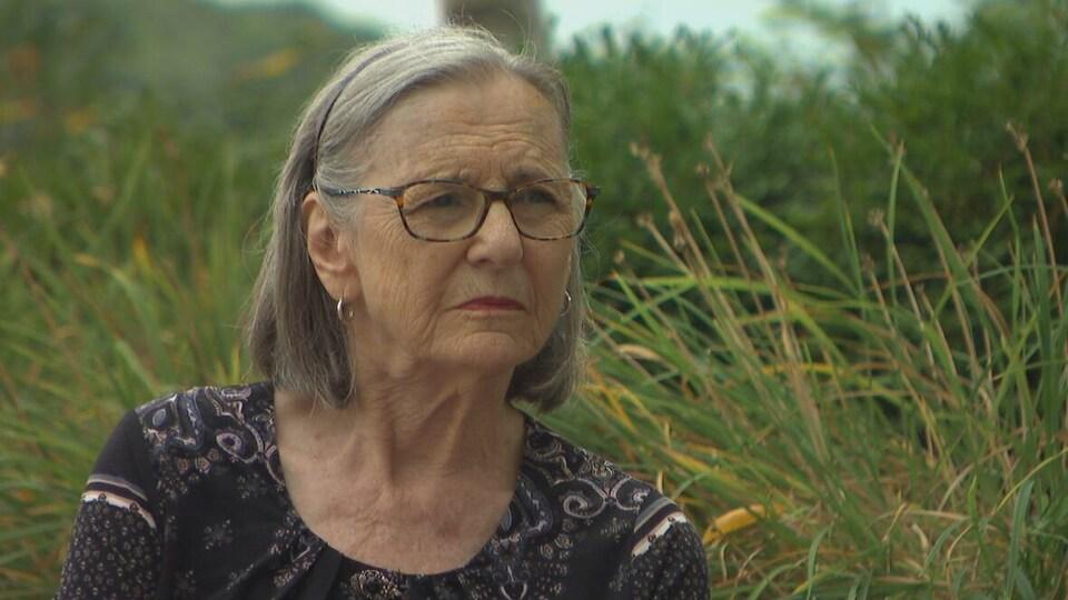 L'épouse de X, Katherine, devant des herbes hautes.