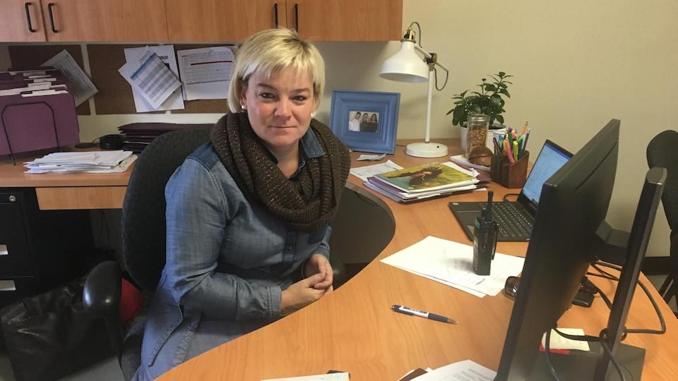Une femme pose derrière son bureau.
