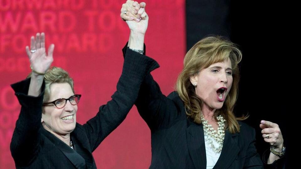 Kathleen Wynne lève les mains dans les airs et célèbre sa victoire.