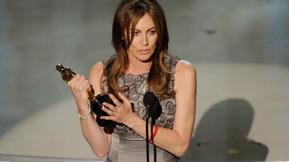 La femme parle devant un micro en tenant la statuette dans ses mains.