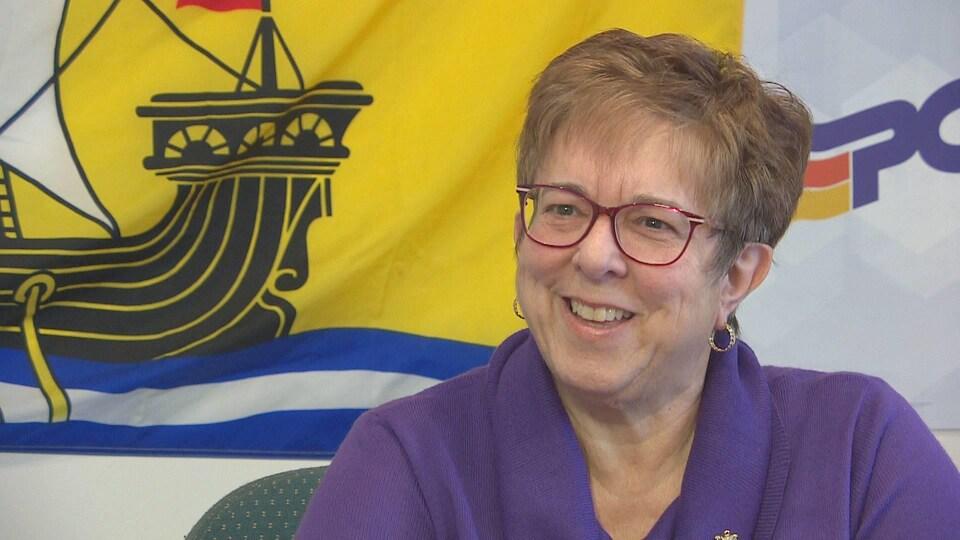Kathy Bockus devant une affiche du Parti progressiste-conservateur et un drapeau du Nouveau-Brunswick.