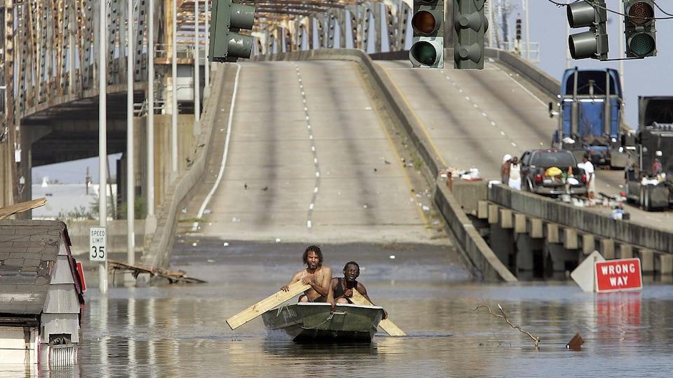 Deux hommes se déplacent en chaloupe au-dessus d'une voie menant à un pont.