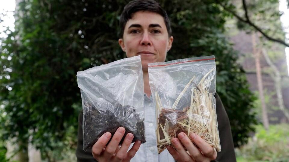 Une femme tend deux sacs en plastique devant elle, l'un avec une matière brune à l'intérieur, l'autre avec de la paille et des copeaux de bois.