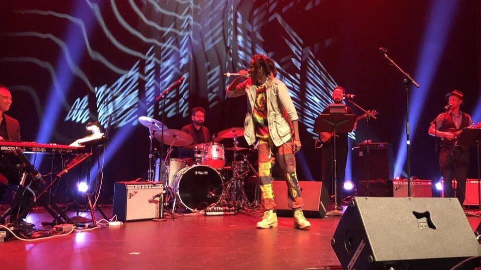 Un homme micro à la main devant des musiciens.