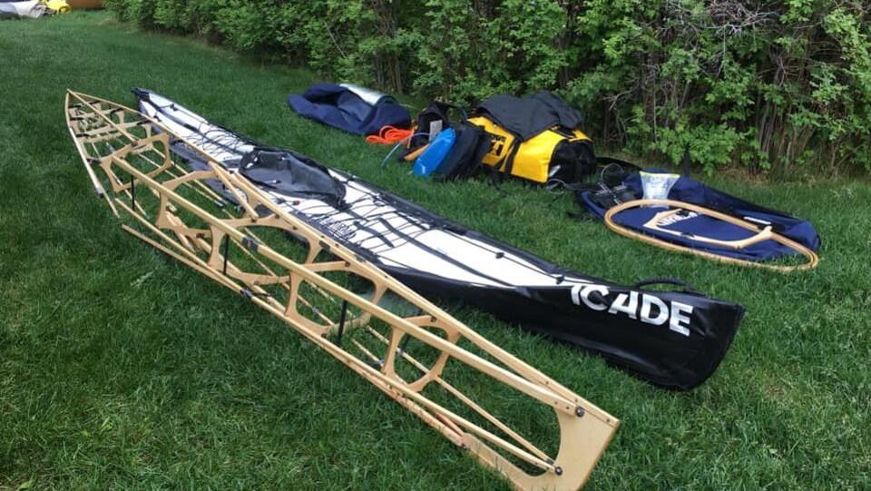 Une charpente de kayak posée dans l'herbe, avec des sacs pour l'expédition à côté, ainsi que le revêtement du kayak.
