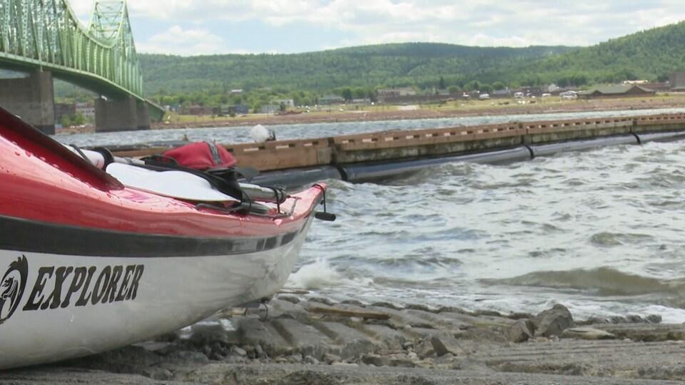 On voit un kayak de très près. Il est en bordure d'un plan d'eau, près de quai.