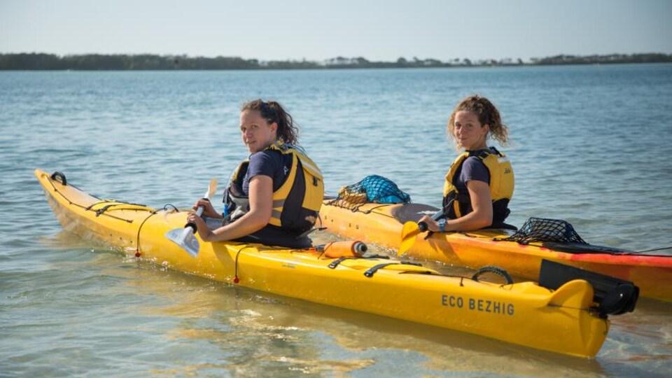 Deux jeunes femmes avec des cheveux frisés retenus par un élastique sont assises chacune dans un kayak, aviron à la main, sur l'eau et regardent en souriant l'objectif.