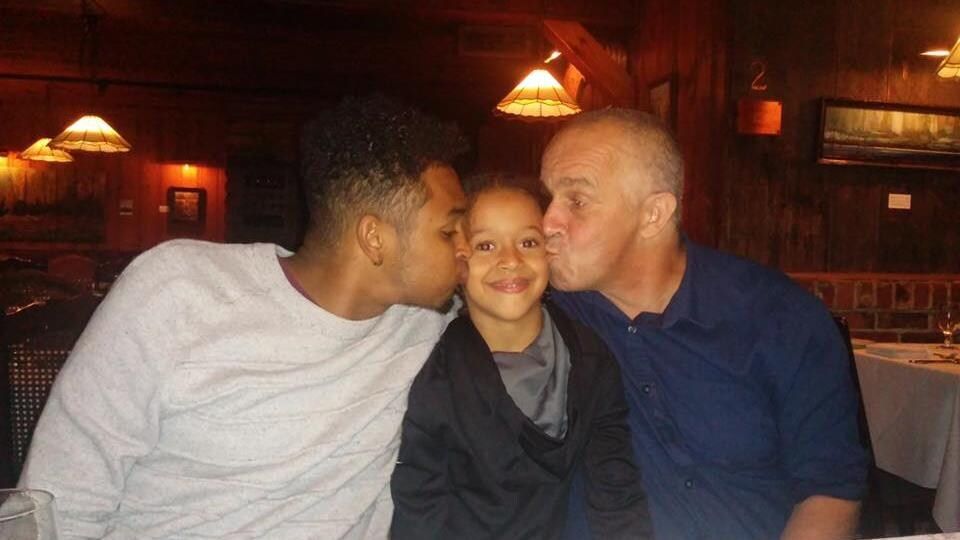Le jeune homme et son père donnent un baiser sur la joue à la petite fille assise entre eux.