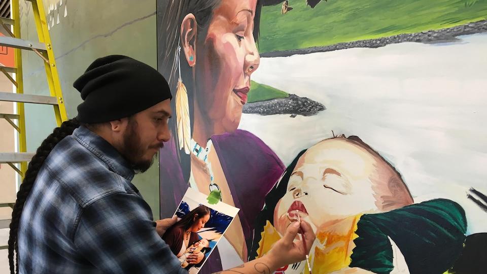 Keegan Starlight peint la bouche d'un bébé tenu dans les bras de sa mère sur la murale, en s'inspirant d'une photo de sa femme et son fils qu'il tient dans sa main.