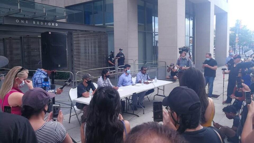 Des gens assis à une table entourés de journalistes et de manifestants, devant un édifice.