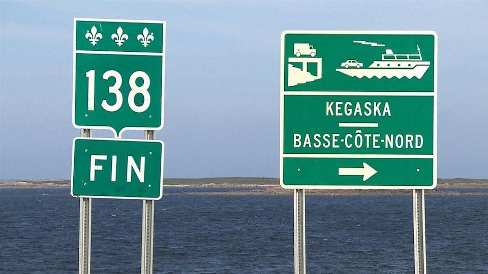 Un panneau annonçant la fin de la route 138 à côté d'un panneau annonçant la traverse Kegaska-Basse-Côte-Nord.