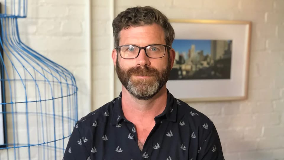 Une homme portant une chemise et des lunettes.