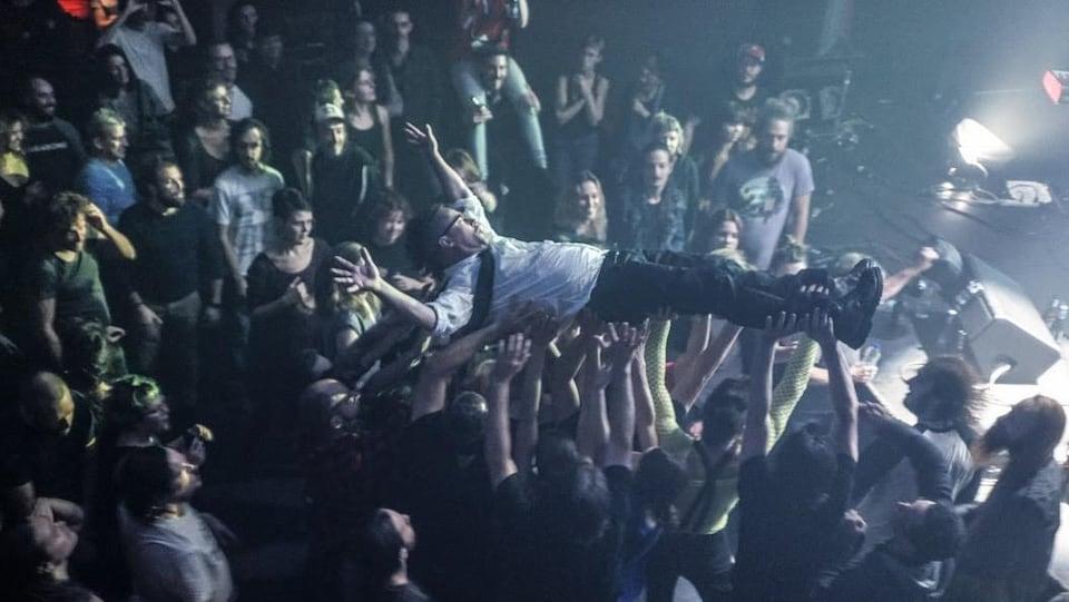 Le chanteur Keith Kouna fait du « bodysurfing » dans la foule.