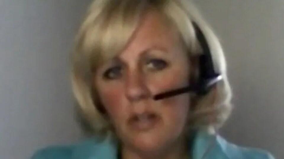 Une femme parle dans un micro rattaché à un casque d'écoute.