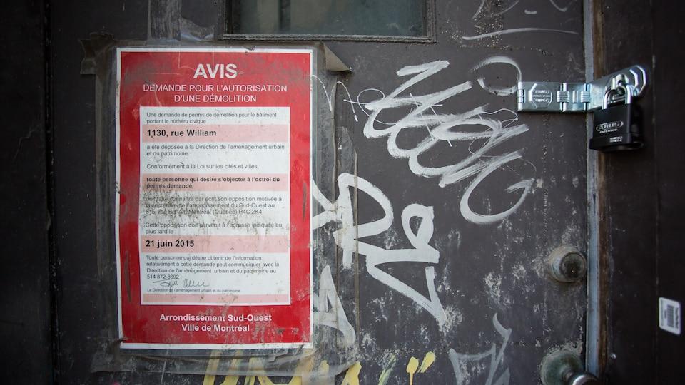 Un avis pour une demande d'autorisation de démolition d'édifice est affichée sur la porte de l'immeuble désaffecté.