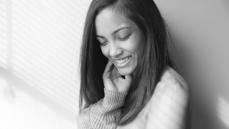 Photo en noir et blanc d'une femme issue de minorité visible, souriant.