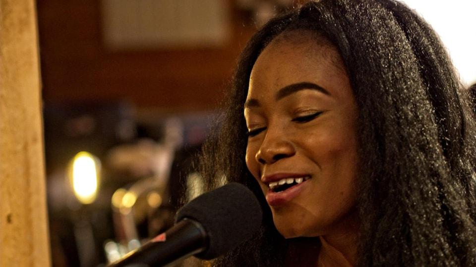 L'auteure-compositrice-intérprète manitobaine, Kelly Bado chante devant un micro.