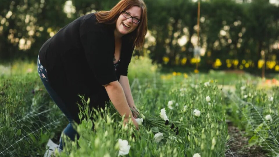 Une femme ramasse des fleurs dans un champ.