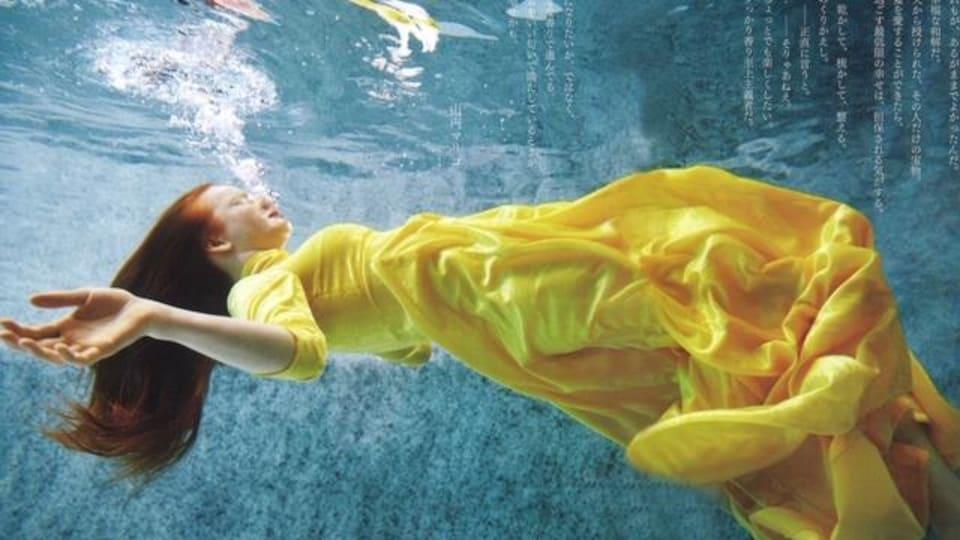 On voit une jeune femme portant une robe jaune.  Elle flotte dans l'eau.