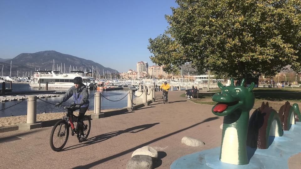 Des cyclistes roulent à côté de la marina et il y a une statue de la créature Ogopogo
