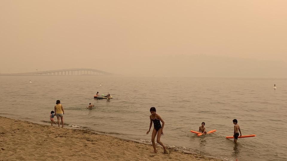 Des enfants jouent au bord du lac Okanagan sous la fumée des feux de forêt qui brouille la vue d'un pont.