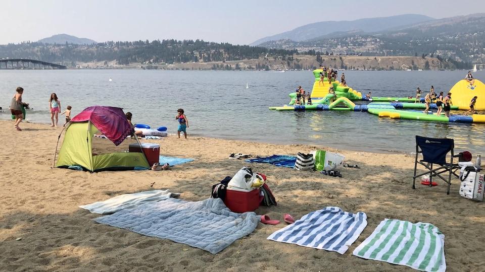 Des serviettes et des activités nautiques sur une plage de Kelowna.