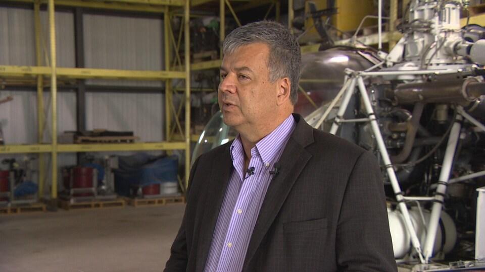 Un homme avec une veston devant un hélicoptère.