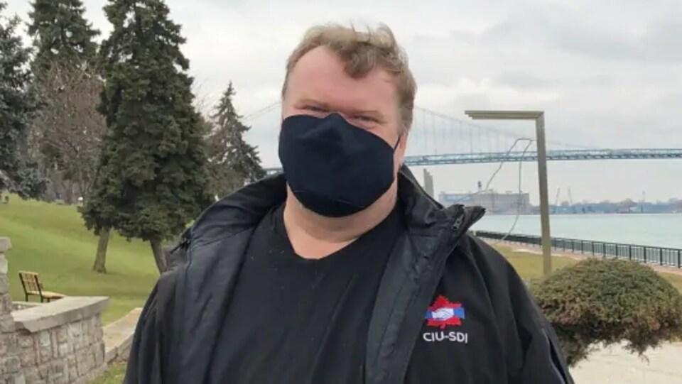 Un homme debout avec un masque qui fait face à la caméra.