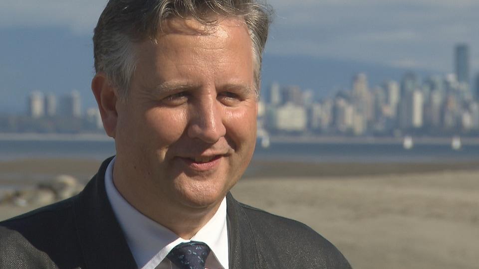 Kennedy Stewart et la ville de Vancouver en arrière-plan, il est sur une plage