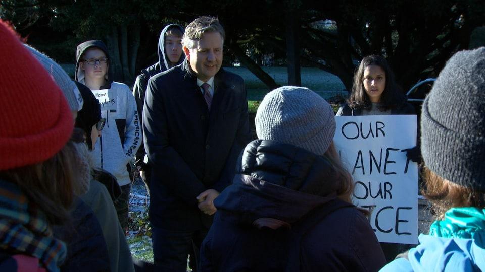 Le maire de Vancouver écoute les questions de quelques jeunes qui tiennent des affiches.